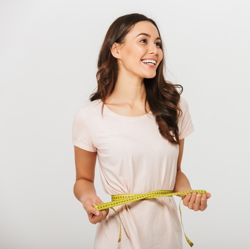 happy young woman with tape measure around her waist