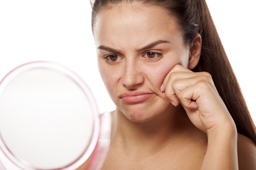 woman staring unhappily at her wrinkles in the mirror
