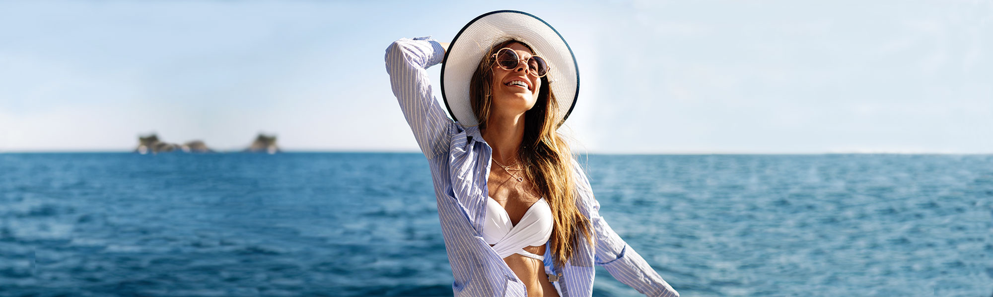 brown haired woman in sunglasses holding a white hat on her head and ocean in the background