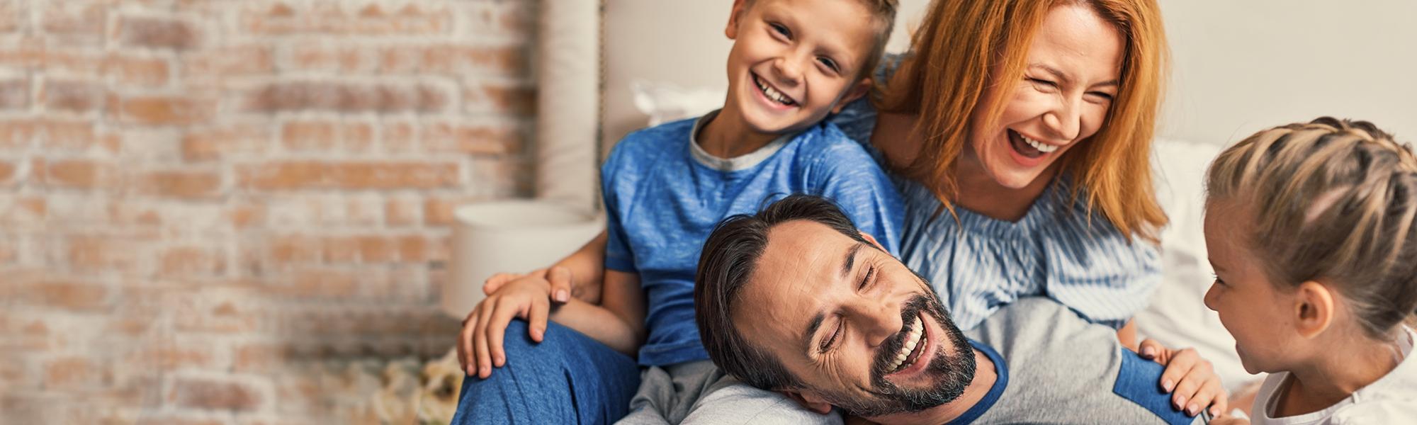 Laughing family enjoying the morning laughing in their pajamas