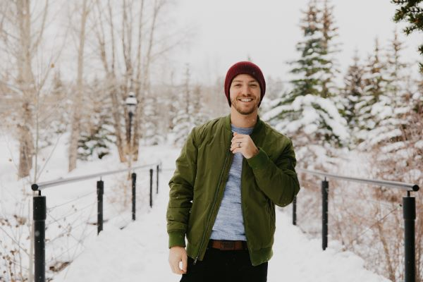 A young man in a green bomber jacket and red beanie stops to smile at the camera on a snowy bridge with trees in the background