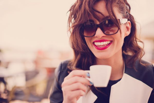 Young woman with styled hair and sunglasses smiles while wearing red lipstick and raising an espresso cup