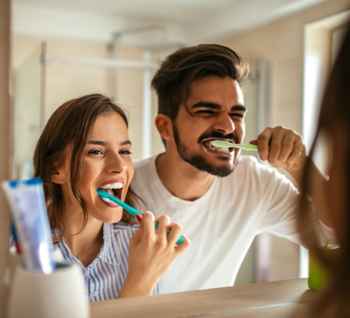 preventative dental care - woman and man brushing teeth