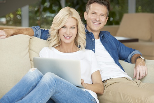smiling middle-aged couple on the couch