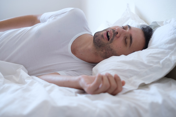 Man laying in bed with mouth open, snoring because of sleep apnea