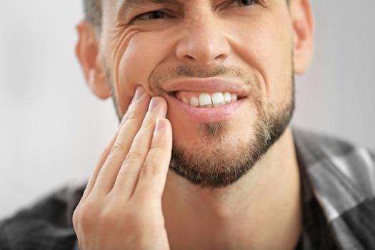 man with toothache touching his cheek and wincing