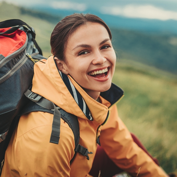 Smiling woman backpacking in the wilderness