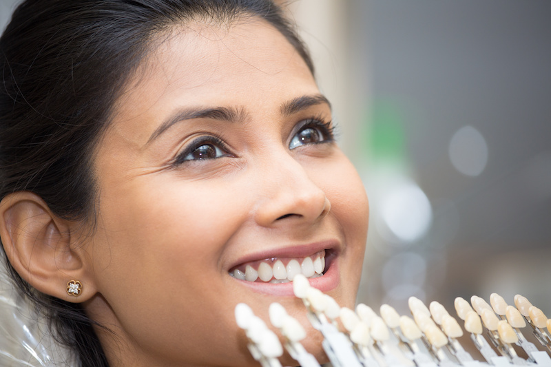 Woman holding porcelain veneers up to her teeth to match the shade