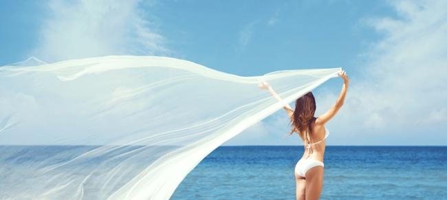 woman in bikini holding long, flowing gossamer sheet on beach
