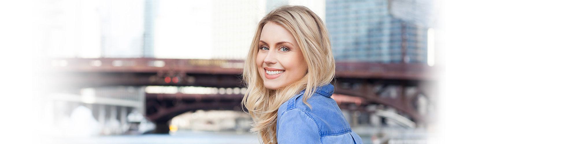 Woman smiling near a bridge