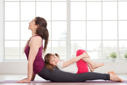 woman doing yoga with her daughter