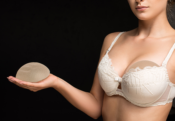Female plastic surgeon in Tulsa has patient hold breast implants.