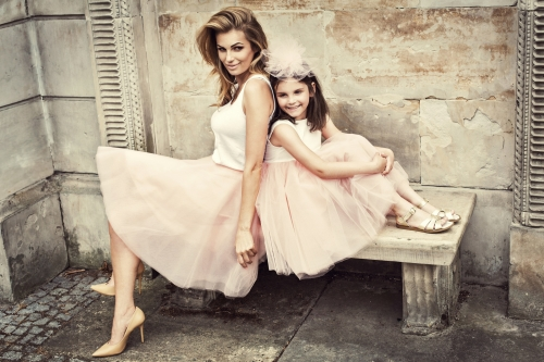 mother and daughter dressed for wedding sitting on a bench