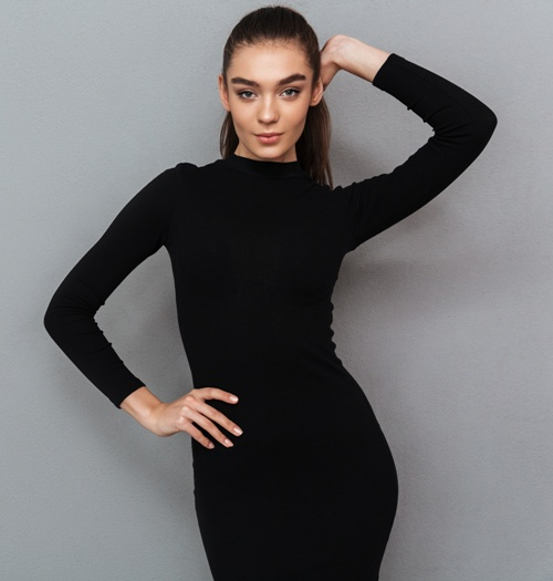 slim woman posing in black dress