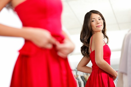 young woman looking in the mirror while trying on dress