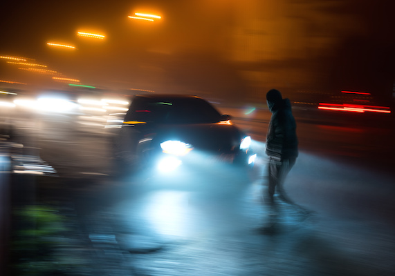 Pedestrian crossing street at night