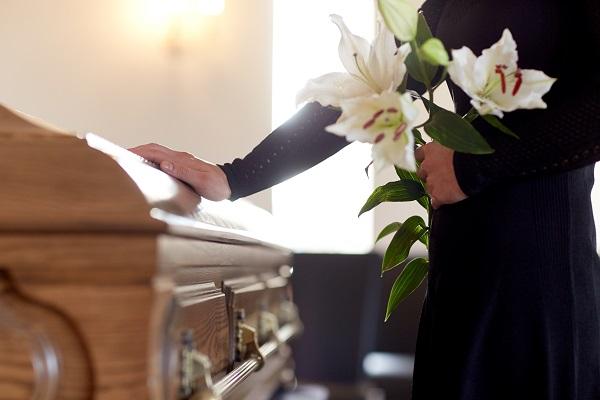 Hand touching a casket