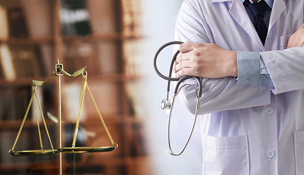 Vancouver doctor stands next to the scale of justice for medical malpractice