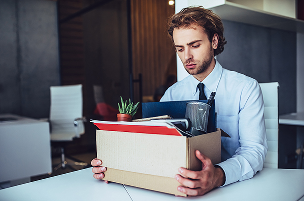 Vancouver man packs box of things after wrongful dismissal.
