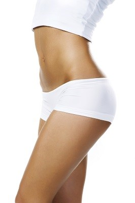 Woman's abdomen, thighs and hips after fat reduction treatment