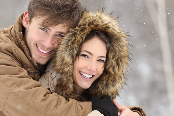 Couple hugging outside while snow is falling