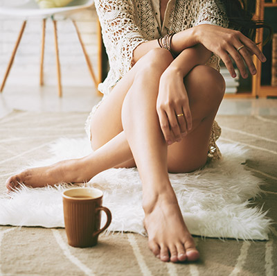 woman with coffee on a rug with her legs crossed