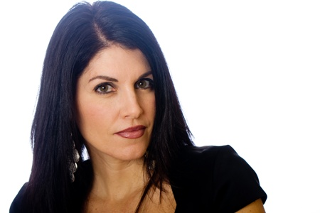 middle-aged woman with dark hair looks at the camera