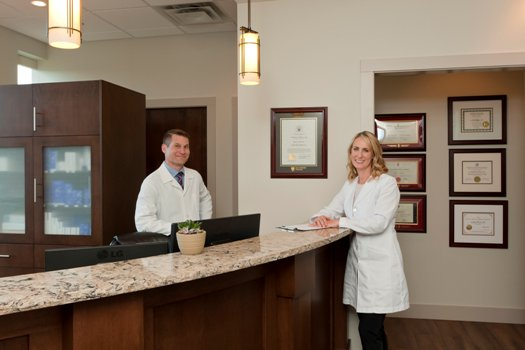 Dr Barnsley and Dr. Weichert at the front desk of Synergy Medical Aesthetics