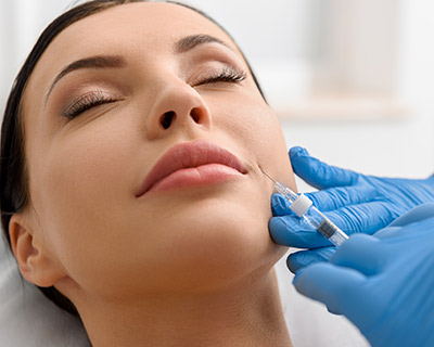 doctor prepares Juvederm facial injection for woman