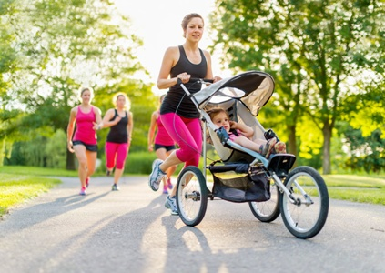 woman pushing daughter in stroller leads joggers in the park