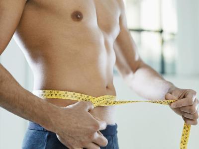man using measuring tape around his waist