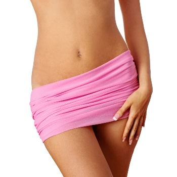 woman with pink cloth around waste bares her toned tummy