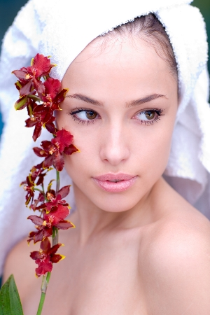woman with towel wrapped around head holding red flowers