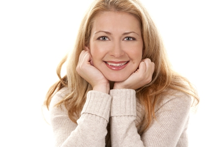 smiling woman rests chin on her hands