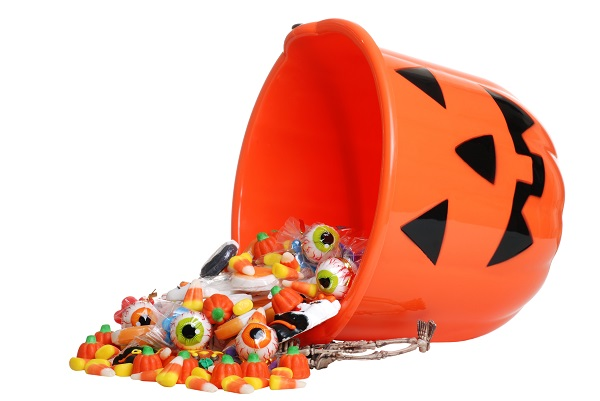 Halloween candy spilling out of an overturned pumpkin bucket on a white background