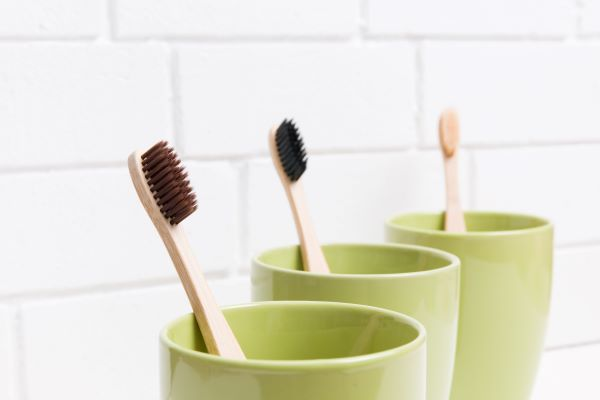 3 toothbrushes placed in 3 separate mugs