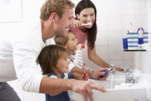 family of four brushing teeth a bathroom sink