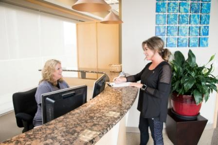 patient completing paperwork at the front desk of The Dentists at Village Pointe