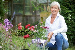 smiling older woman tending flowers in garden