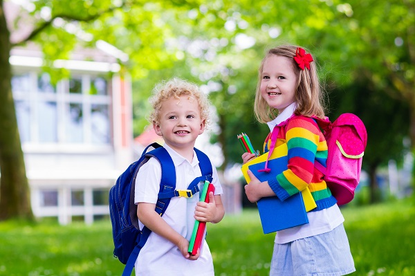 Two young children walking home from school wearing backpacks