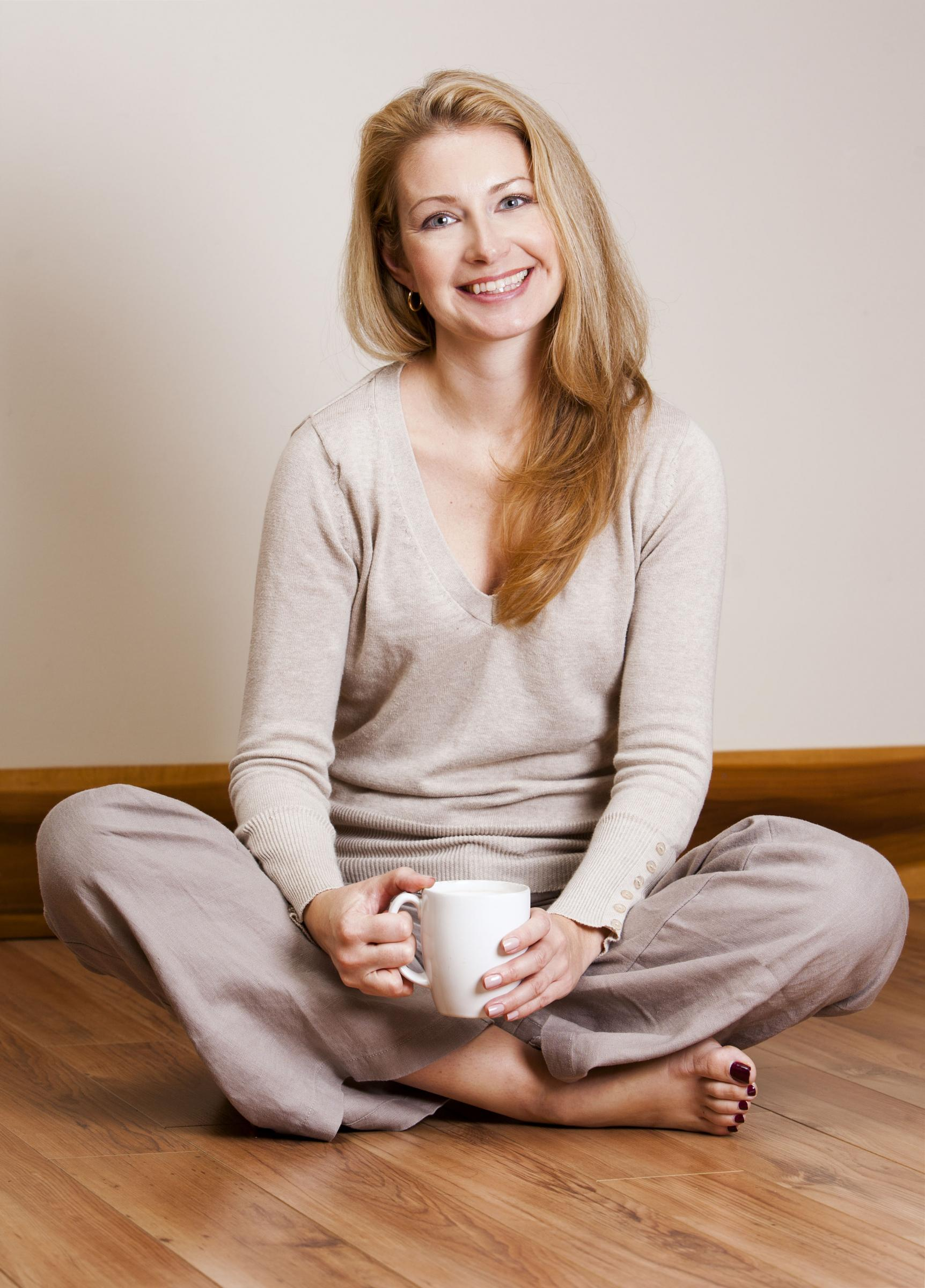 smiling woman sitting cross-legged on the floor holding coffee cup