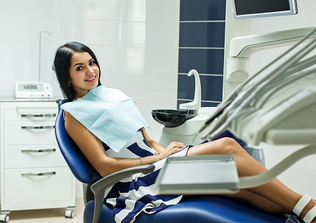 Young woman smiling while seated in the dental treatment chair in Omaha
