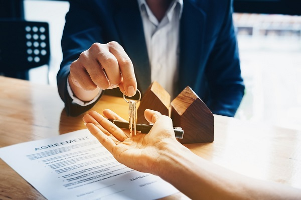 Home buyer receiving keys after signing a sales agreement