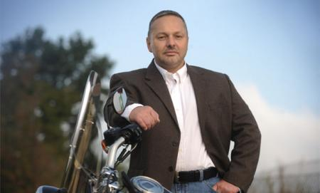 Attorney Mark Troy standing next to his motorcycle
