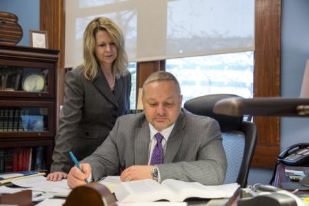 Mark Troy and staff member reviewing legal documents