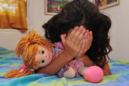crying young girl with doll hiding her face in her hands