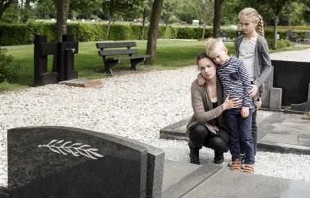 mom and kids visiting headstone in graveyard