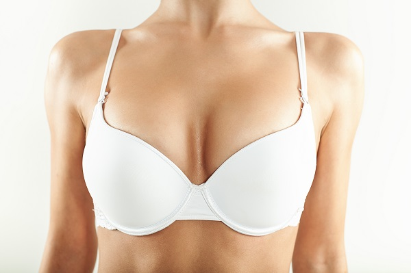 Close-up of a woman's breasts in a white bra after breast lift surgery