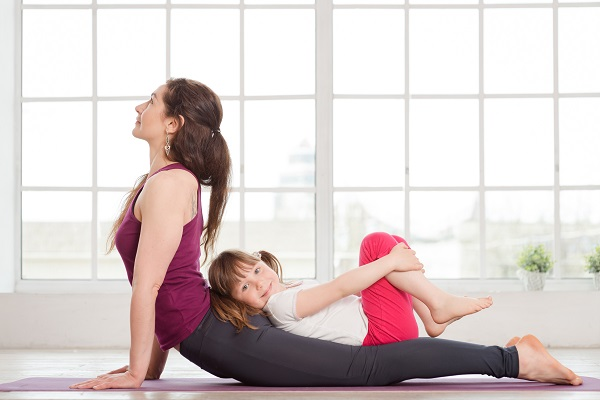 Mom doing yoga with young daughter
