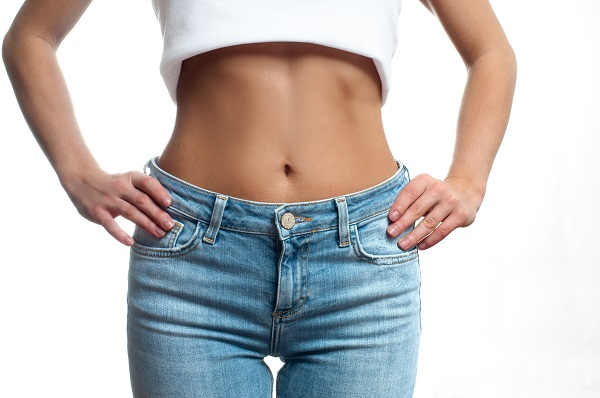 Image of a woman's flat belly with her shirt lifted up and in jeans